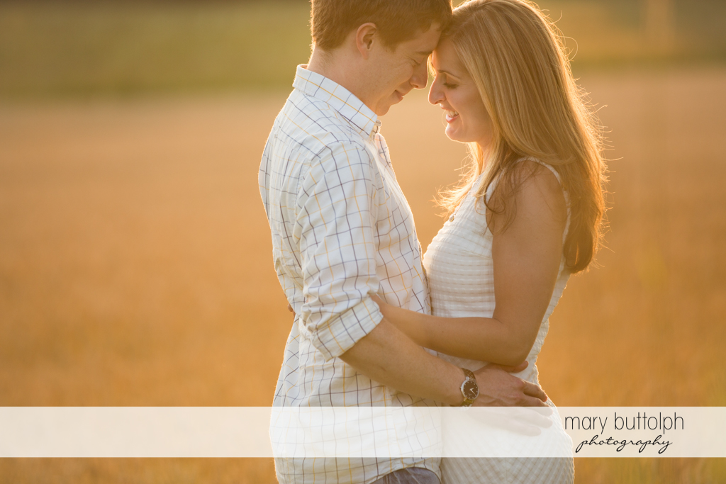Couple embrace in a wheat field at Skaneateles Engagement