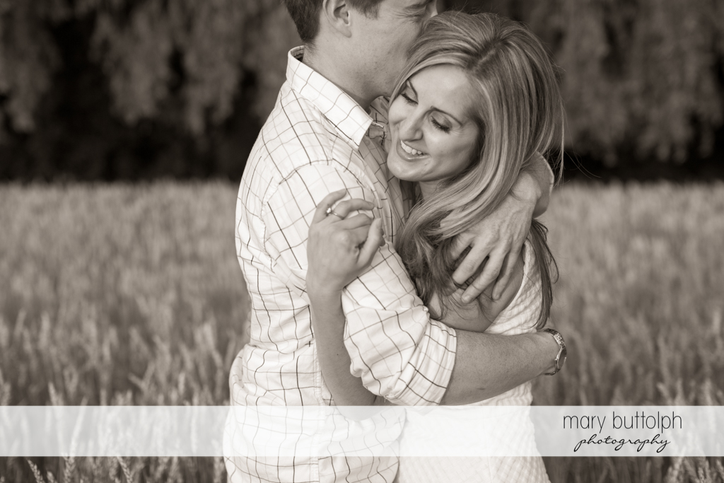 Couple show their love in a wheat field at Skaneateles Engagement
