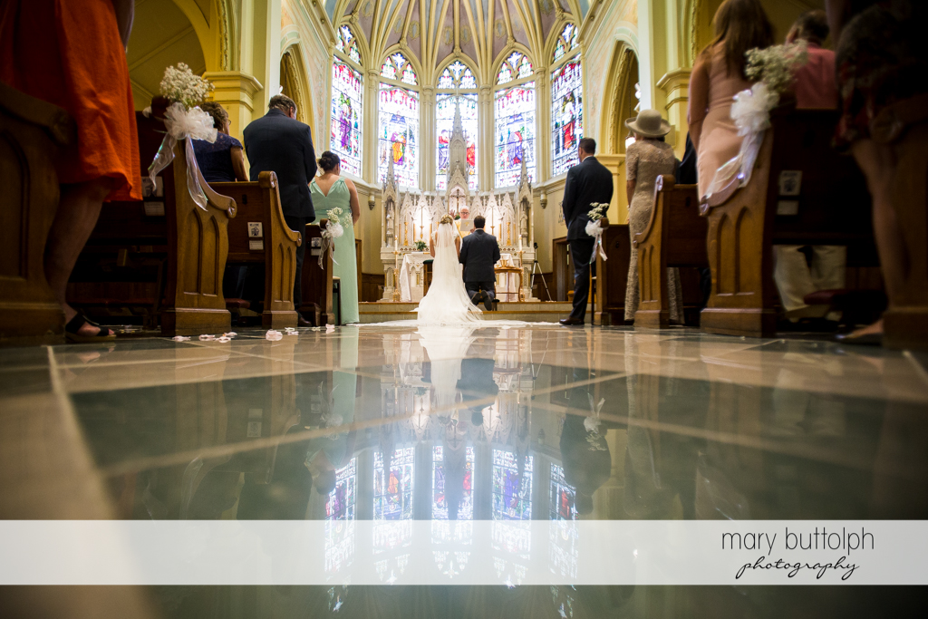 Couple kneel in front of the altar at Emerson Park Pavilion Wedding