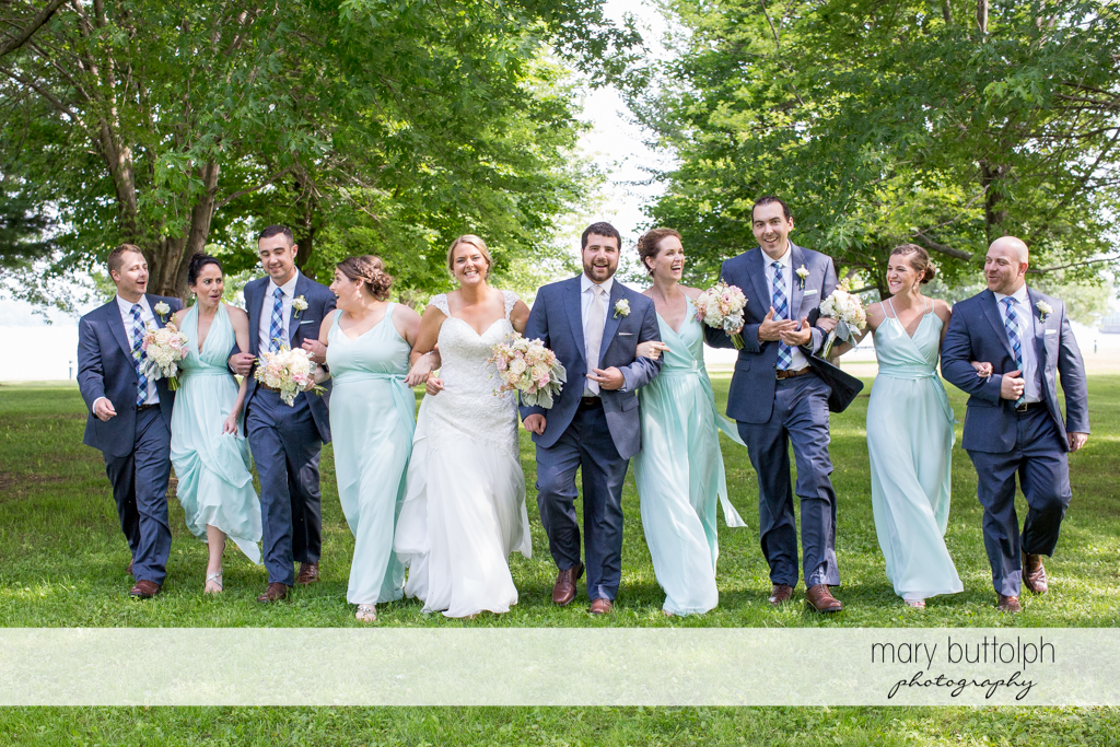 The wedding party walk towards the camera in the garden at Emerson Park Pavilion Wedding