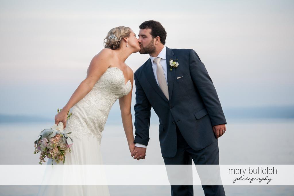 Couple share a kiss near the lake at Emerson Park Pavilion Wedding
