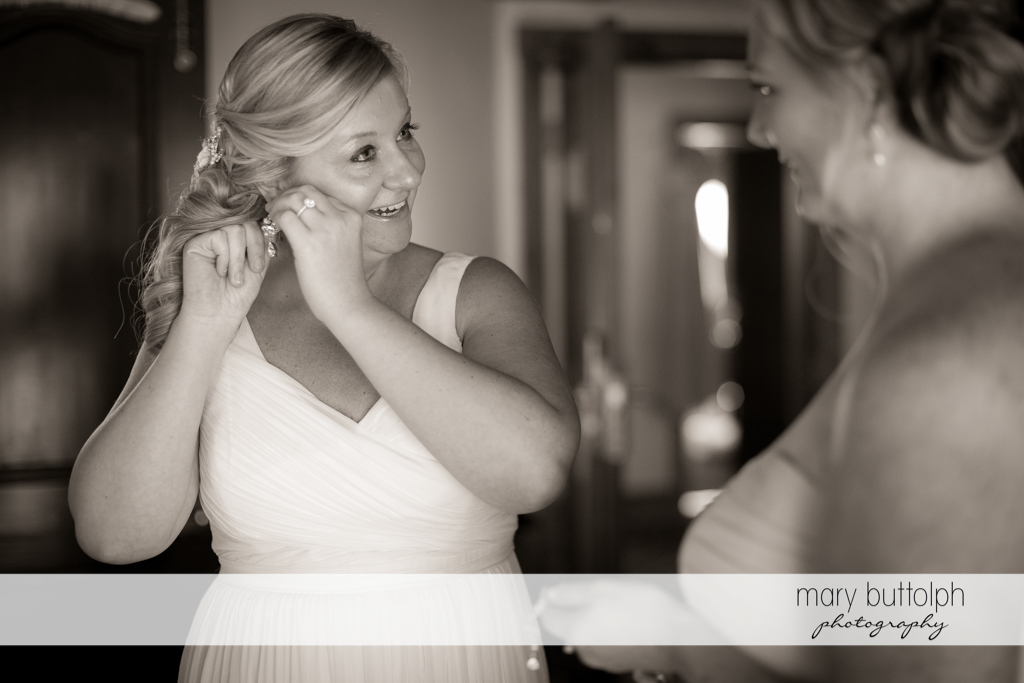 Bride fixes her earring while talking to a guest at Emerson Park Pavilion Wedding