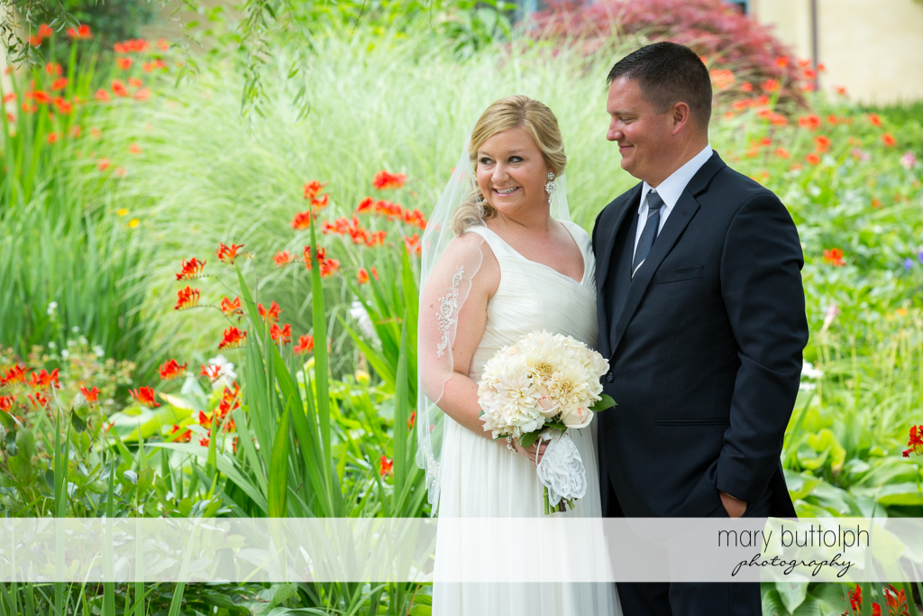 Couple are surrounded by flowers in the garden at Emerson Park Pavilion Wedding