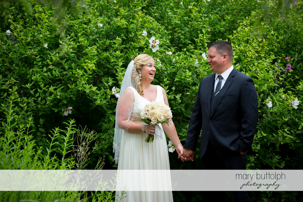 Couple hold hands in the garden at Emerson Park Pavilion Wedding
