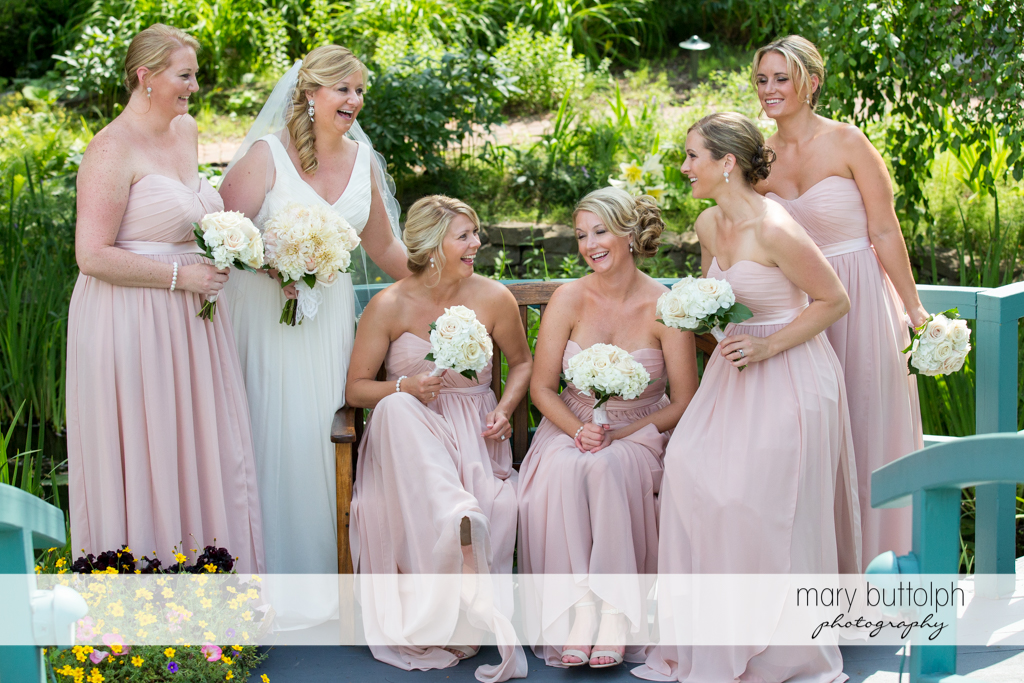 Bride and her bridesmaids share a happy moment in the garden at Emerson Park Pavilion Wedding