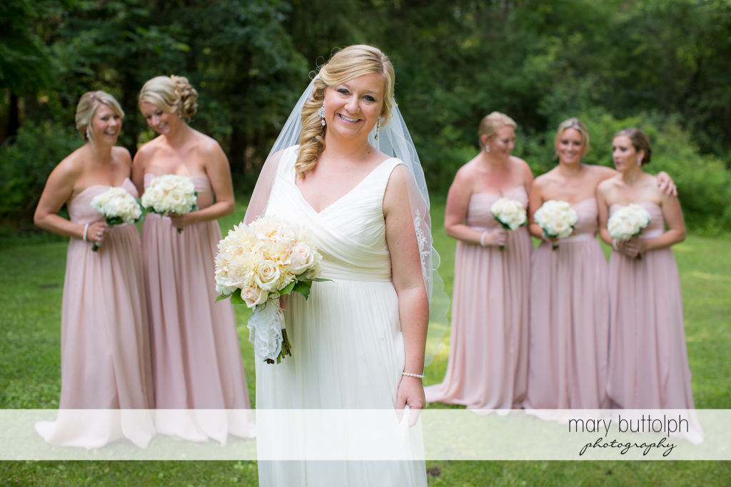 Bride and her bridesmaids pose for posterity in the garden at Emerson Park Pavilion Wedding