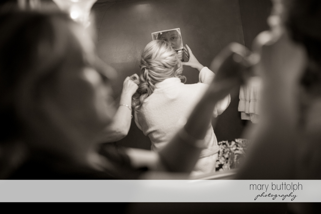 Bride looks in the mirror as the bridemaid's hair is being fixed at Emerson Park Pavilion Wedding