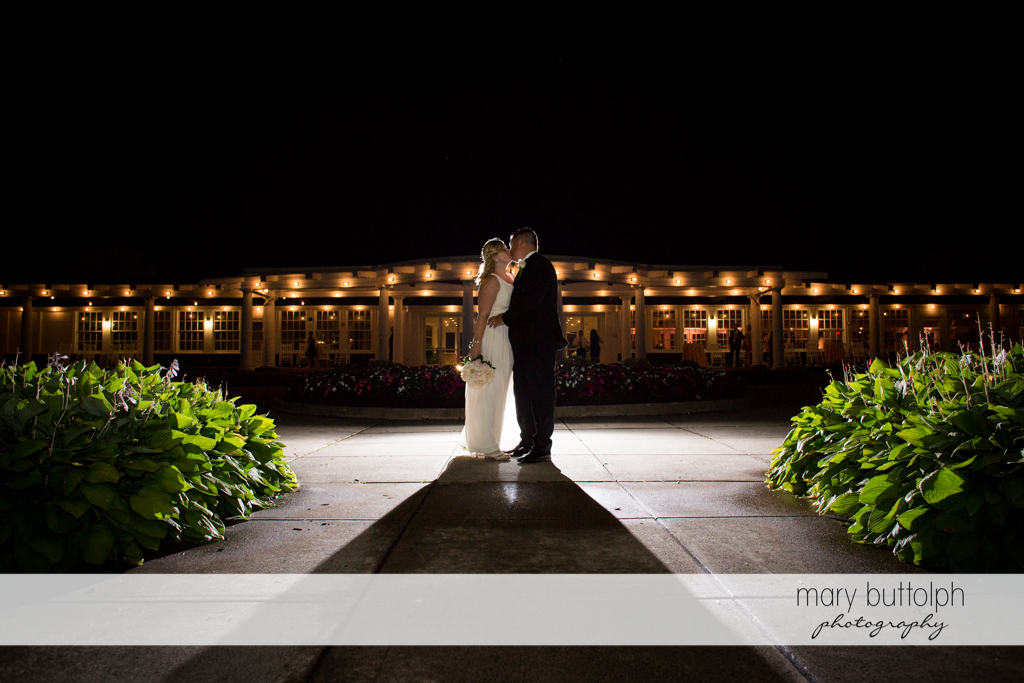 Couple kiss in the moonlight in front of the wedding reception at Emerson Park Pavilion Wedding