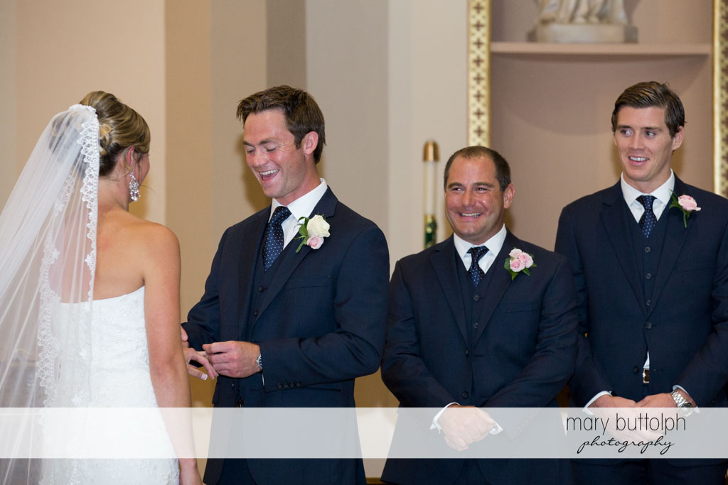 Groom slips the ring on the bride's finger as the groomsmen look on at Skaneateles Country Club Wedding