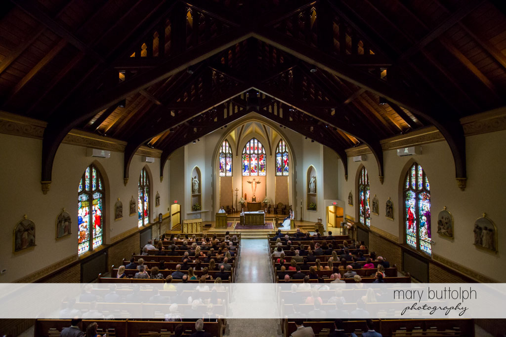 Long shot of people inside the church during the couple's wedding at Skaneateles Country Club Wedding