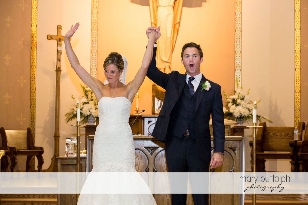 Couple raise their hands in front of the altar at Skaneateles Country Club Wedding