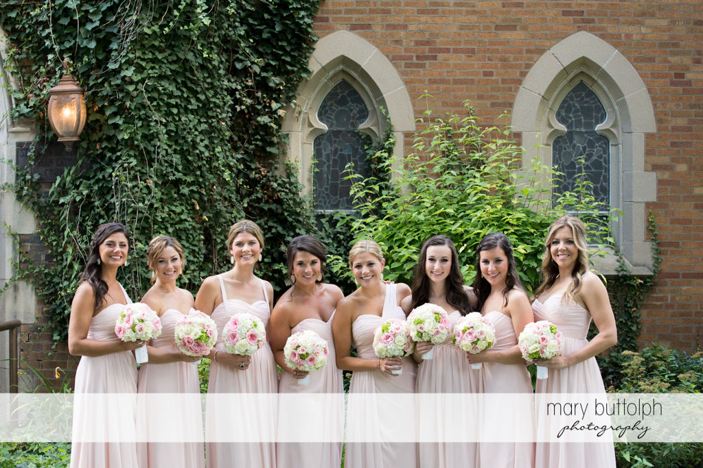 Bride and bridesmaids holding bouquets pose in front of the church at Skaneateles Country Club Wedding