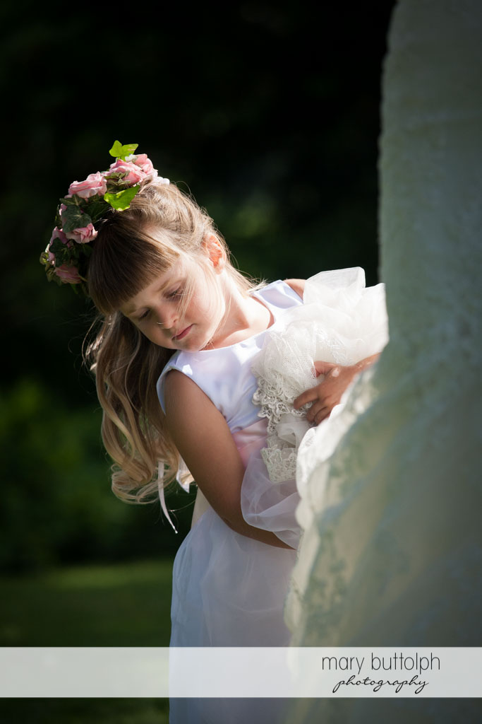 Young girl with wreath holds the bride's wedding gown at Skaneateles Country Club Wedding
