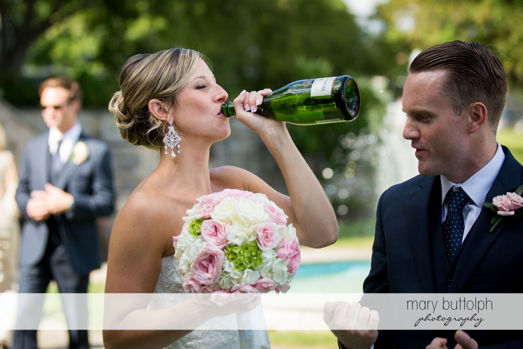 Bride with bouquet drinks champagne in the garden at Skaneateles Country Club Wedding