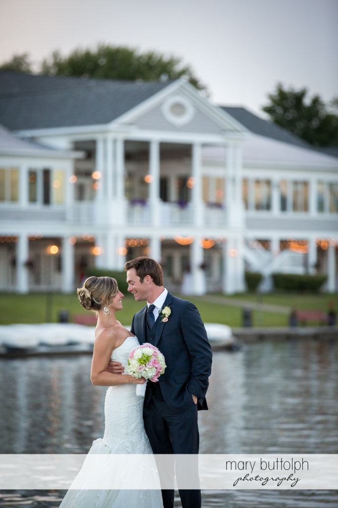 Couple stand in front of the wedding venue by the lake at Skaneateles Country Club Wedding