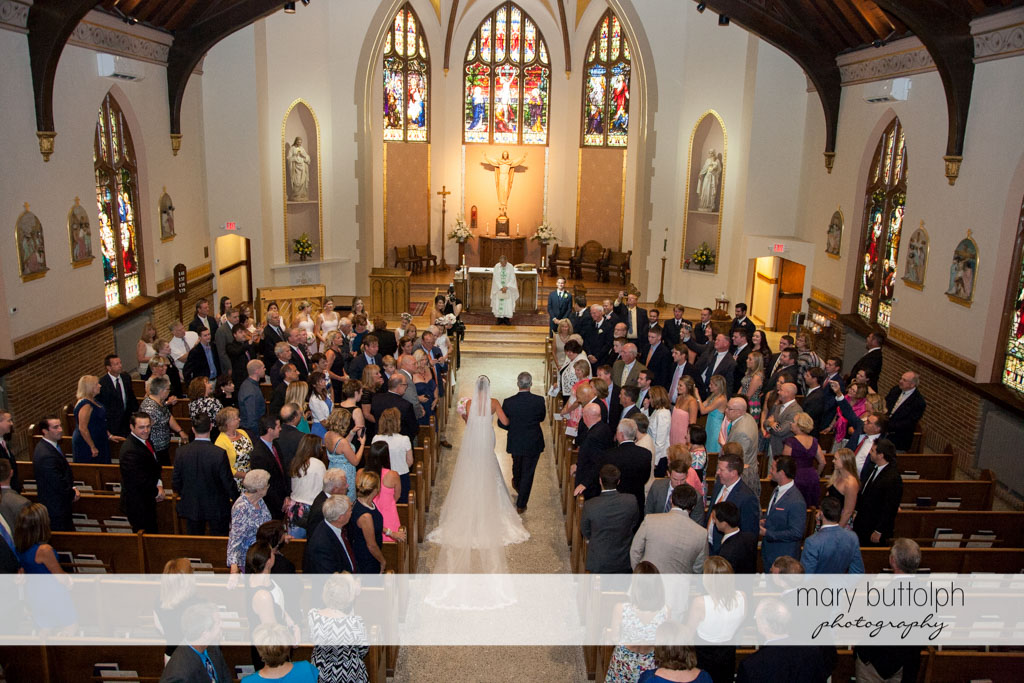 Bride and her father approach the altar as guests look on at Skaneateles Country Club Wedding