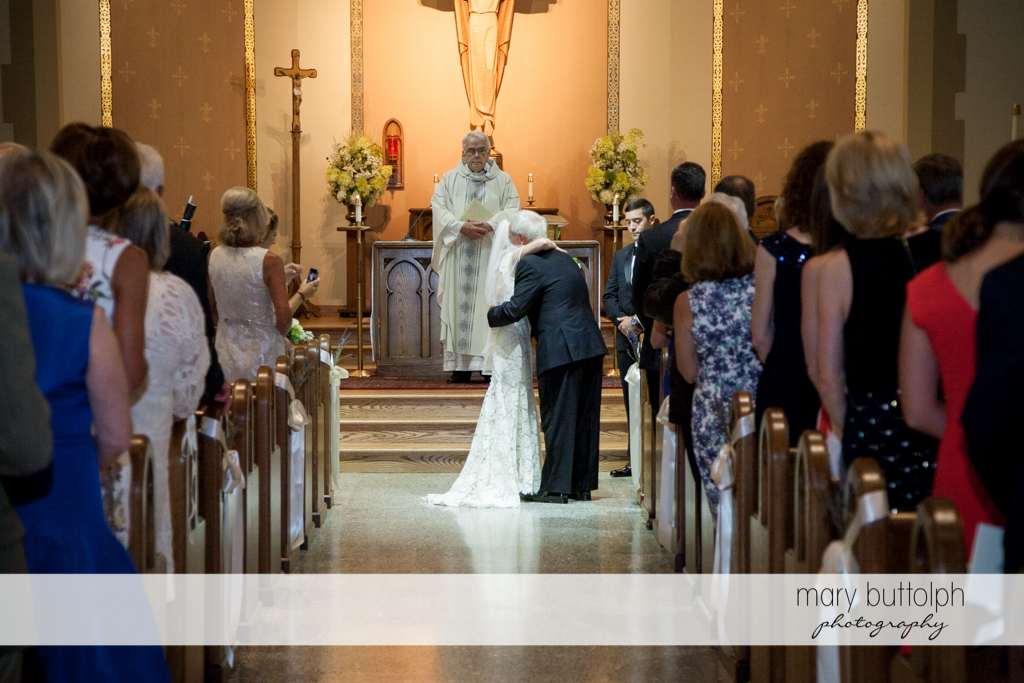 Bride embraces her father in front of the priest at Skaneateles Country Club Wedding
