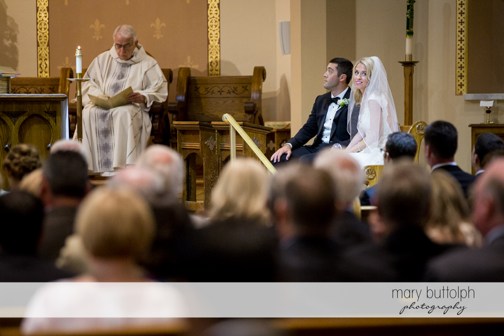 Bride looks at the audience while the groom watches the priest at Skaneateles Country Club Wedding