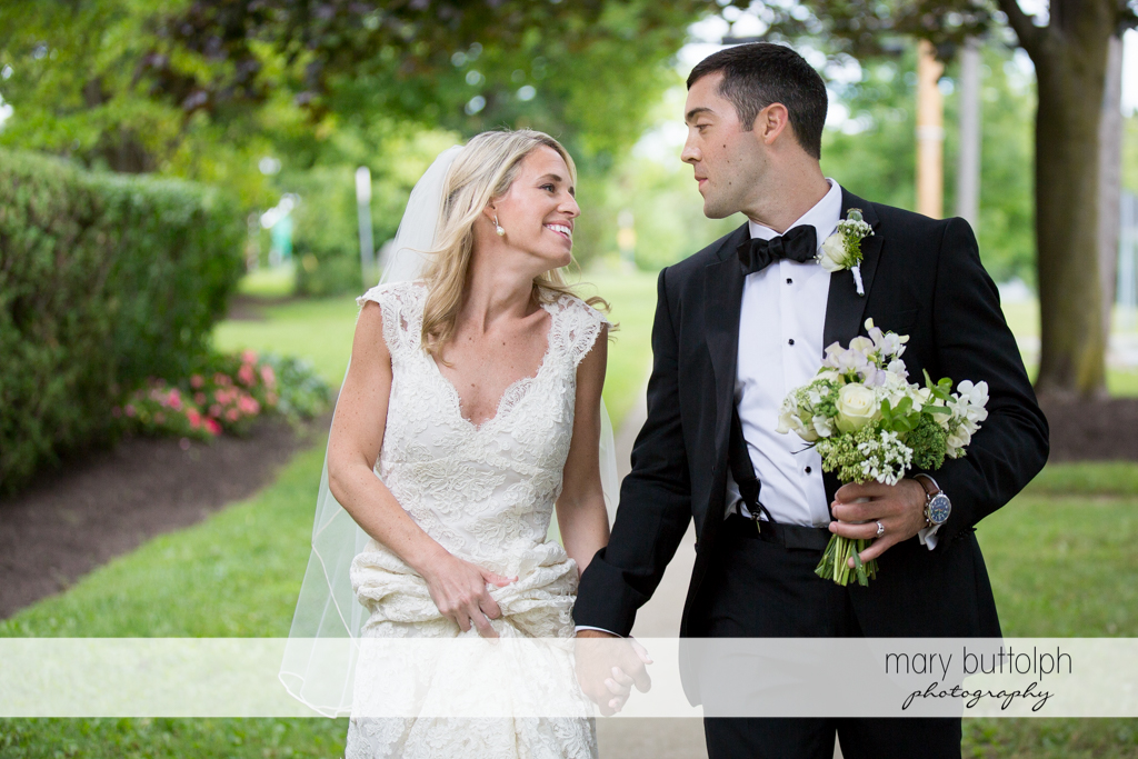Couple face each other as they stroll in the garden at Skaneateles Country Club Wedding