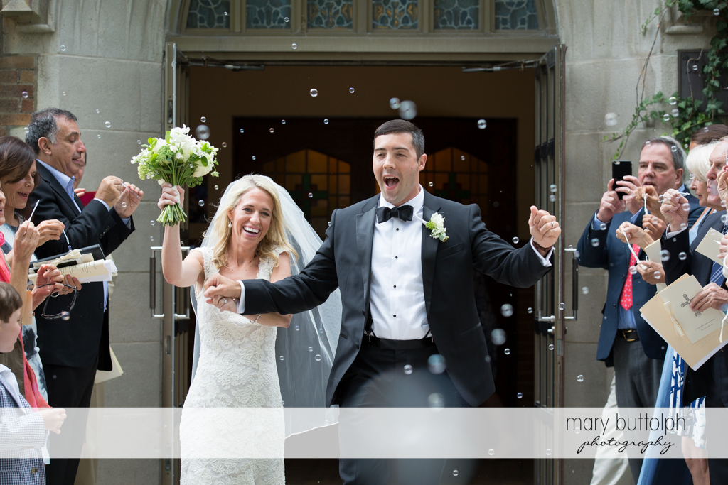 Couple get a bubble shower as they leave the church at Skaneateles Country Club Wedding
