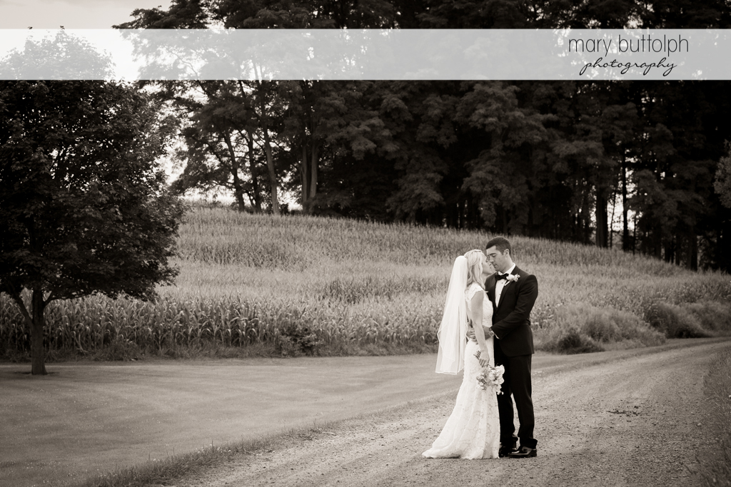 Couple rub noses on the road at Skaneateles Country Club Wedding