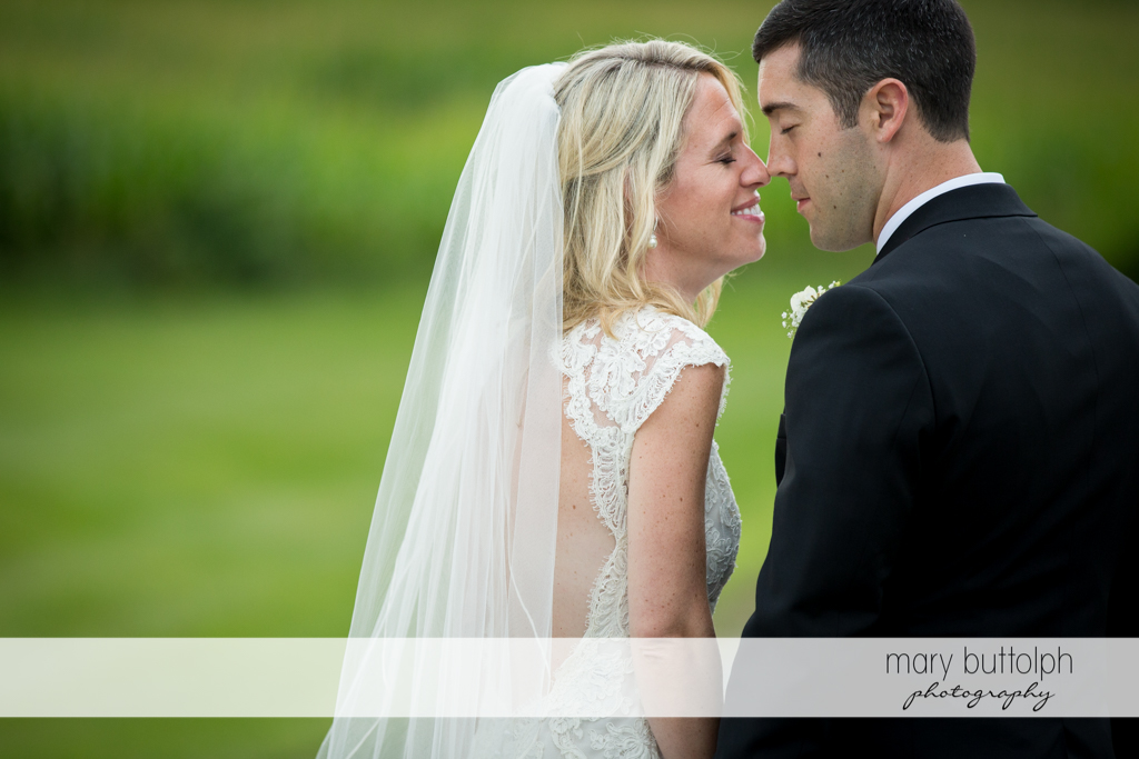 Couple rub noses in the garden at Skaneateles Country Club Wedding