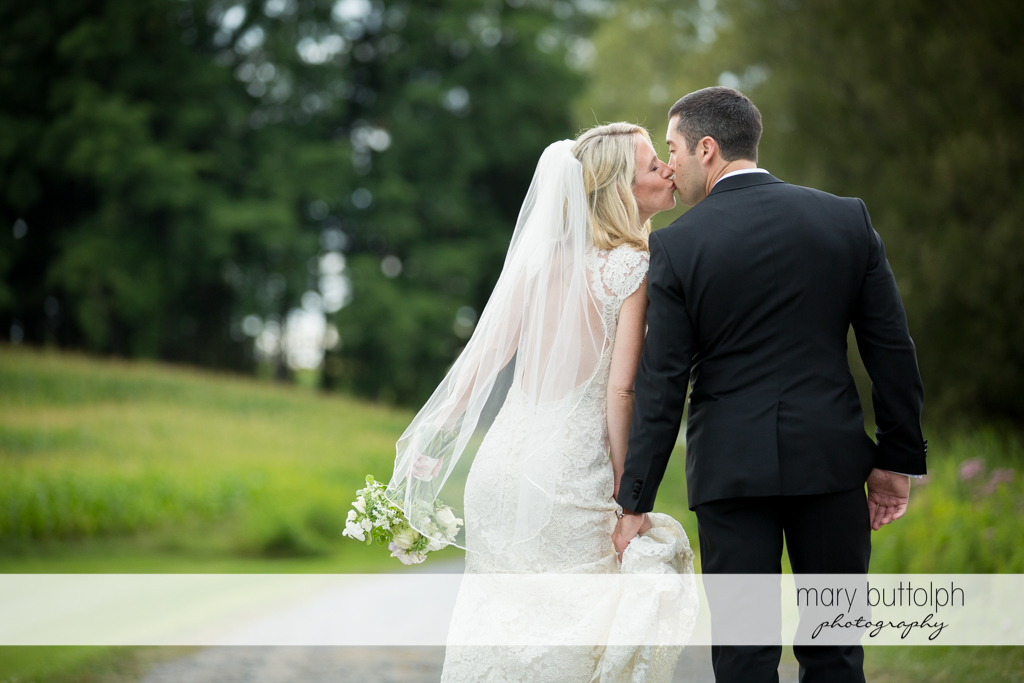 Couple kiss as they walk down the road at Skaneateles Country Club Wedding