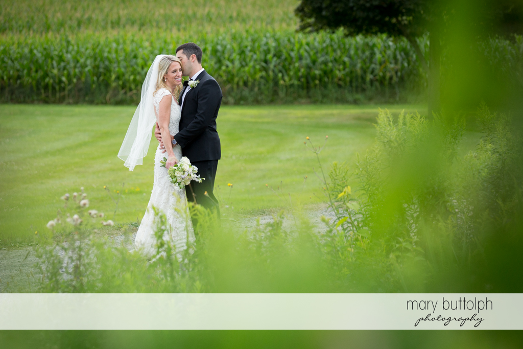 Couple pose in the field at Skaneateles Country Club Wedding