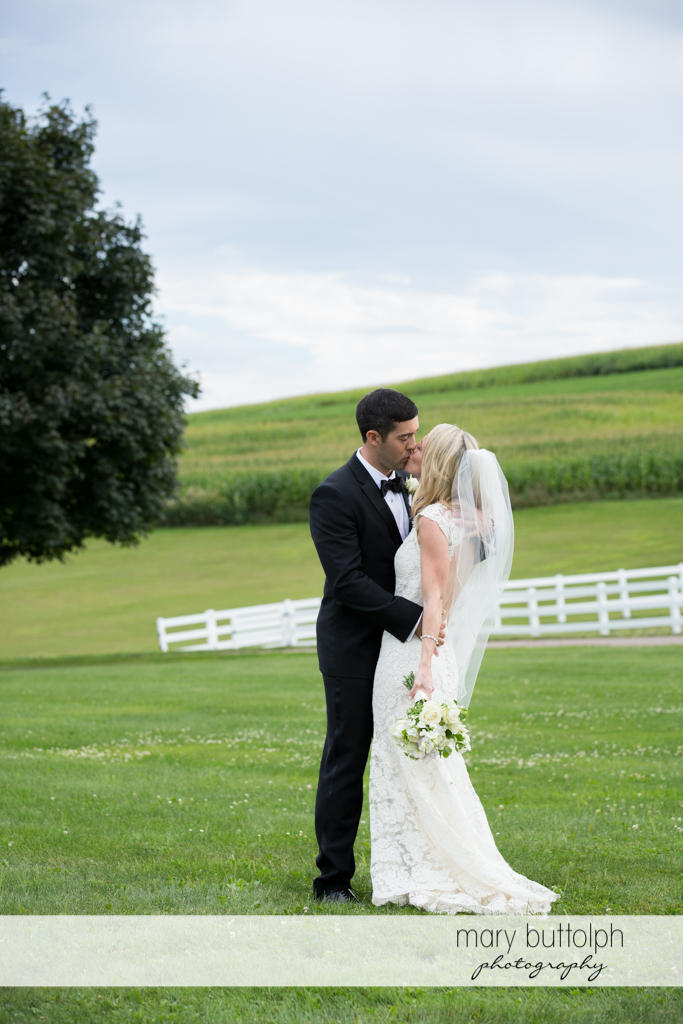 Couple kiss on the field at Skaneateles Country Club Wedding