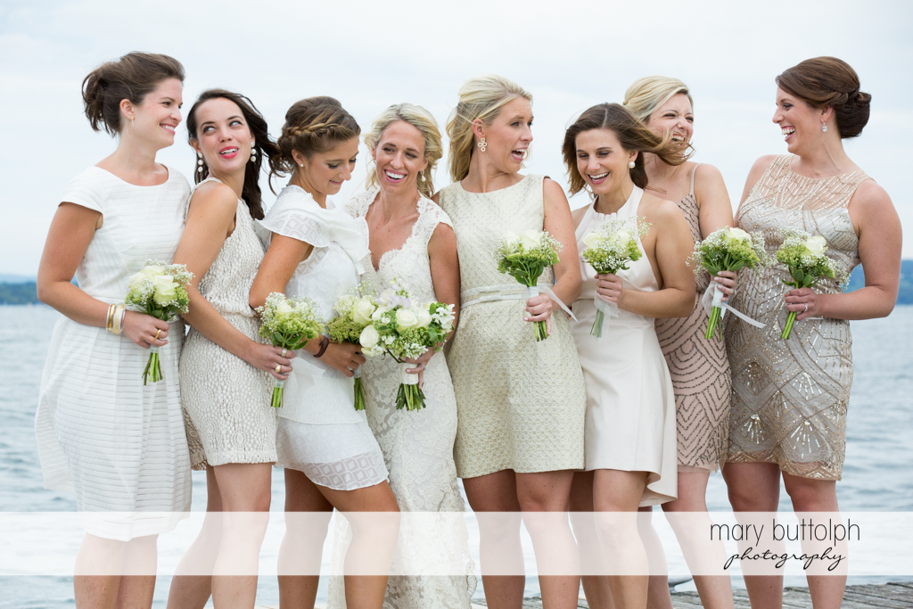 The bride and her bridesmaids with flowers in front of the lake at Skaneateles Country Club Wedding
