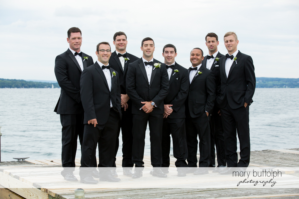 The groom and groomsmen pose by the lake at Skaneateles Country Club Wedding