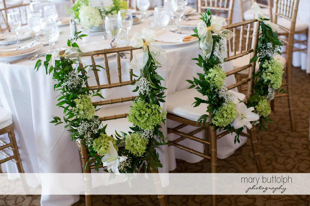 Garlands of flowers decorate the chairs at the wedding venue at Skaneateles Country Club Wedding