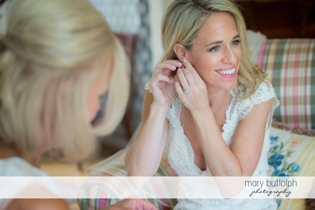 Bride puts on her earring at Skaneateles Country Club Wedding
