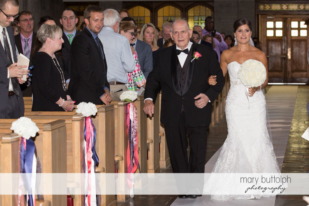 Bride and her father walk down the aisle as guests look on at Turning Stone Resort Casino Wedding