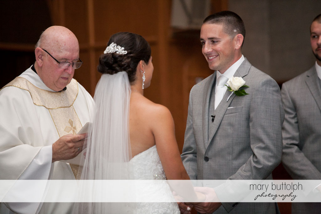 Couple face each other in front of the priest at Turning Stone Resort Casino Wedding