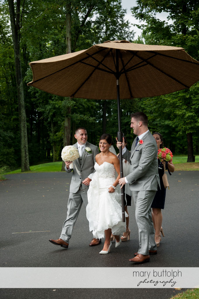 Groomsman shields couple from the heat with a big umbrella at Turning Stone Resort Casino Wedding