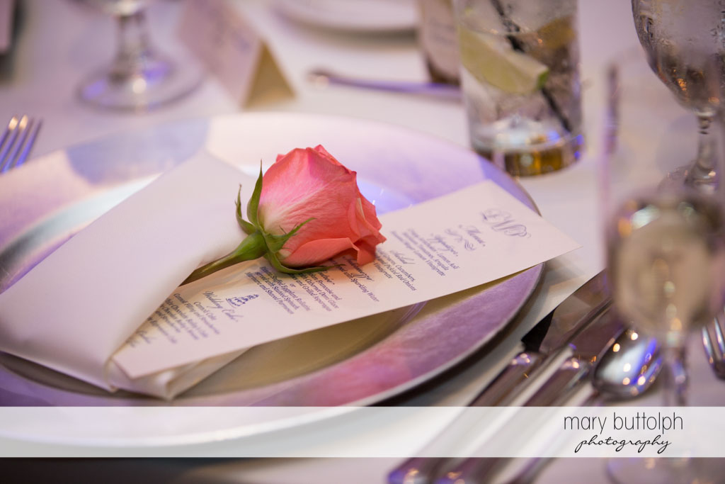 A rose is tucked under a napkin together with the menu atTurning Stone Resort Casino Wedding
