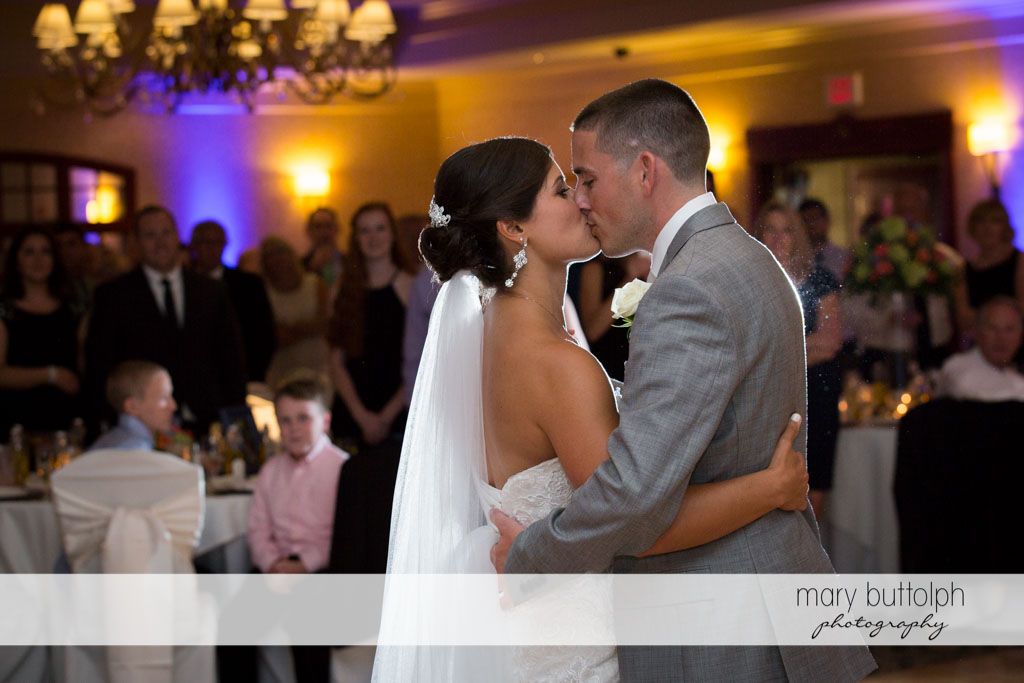 Couple kiss in front of guests at the wedding reception at Turning Stone Resort Casino Wedding