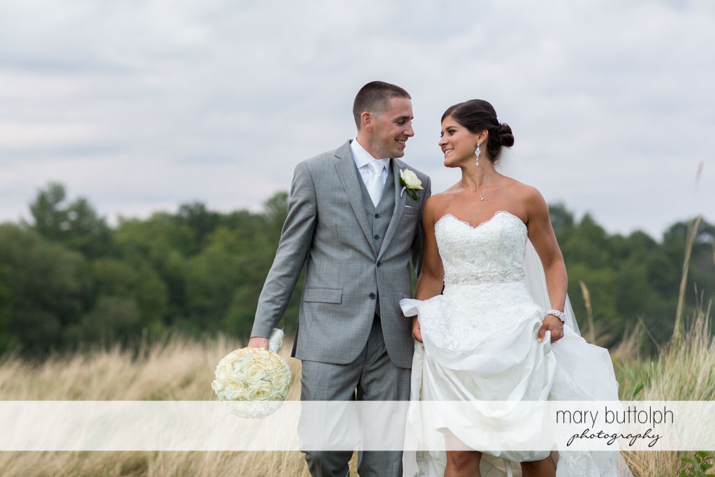 Couple stroll in the field at Turning Stone Resort Casino Wedding