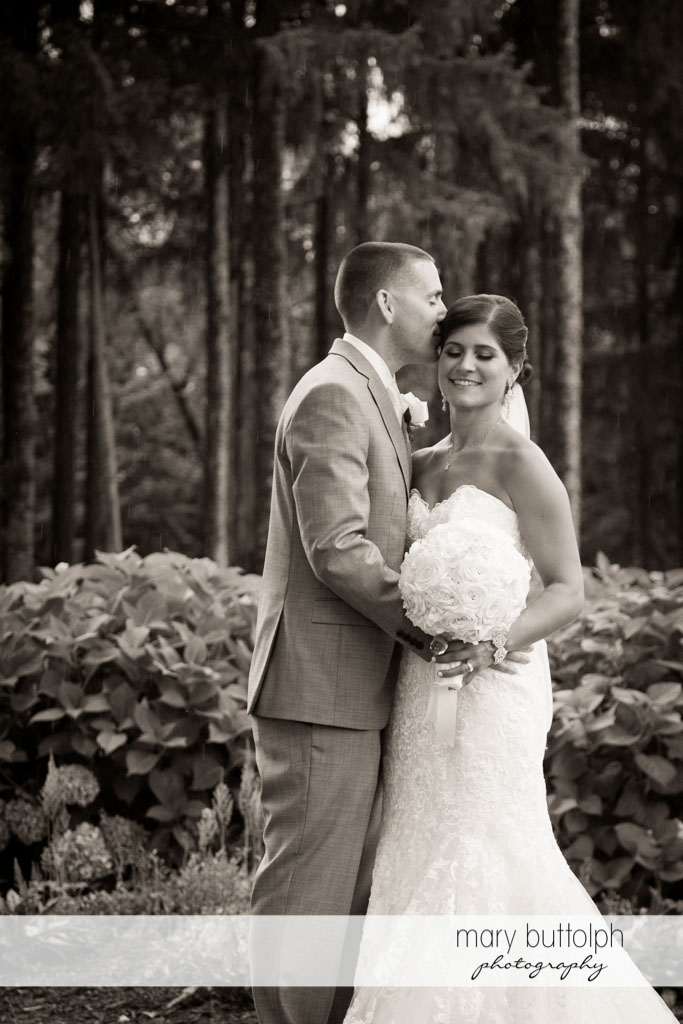 Groom kisses the bride in the woods at Turning Stone Resort Casino Wedding
