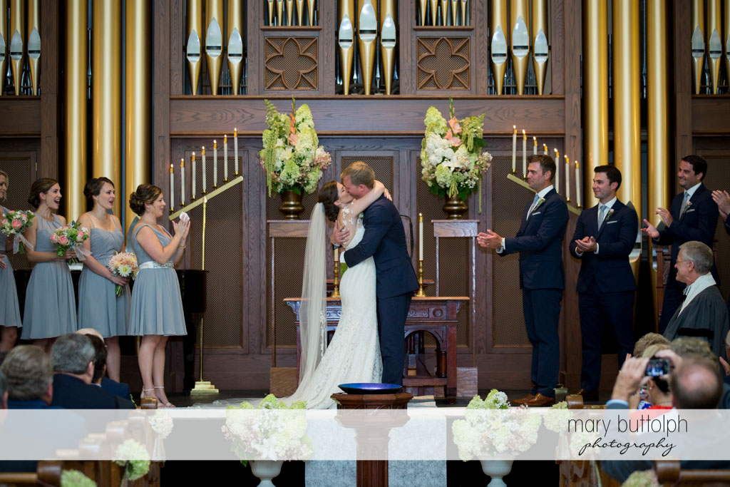 Couple kiss in front of the altar as the wedding party and guests look on at Skaneateles Country Club Wedding