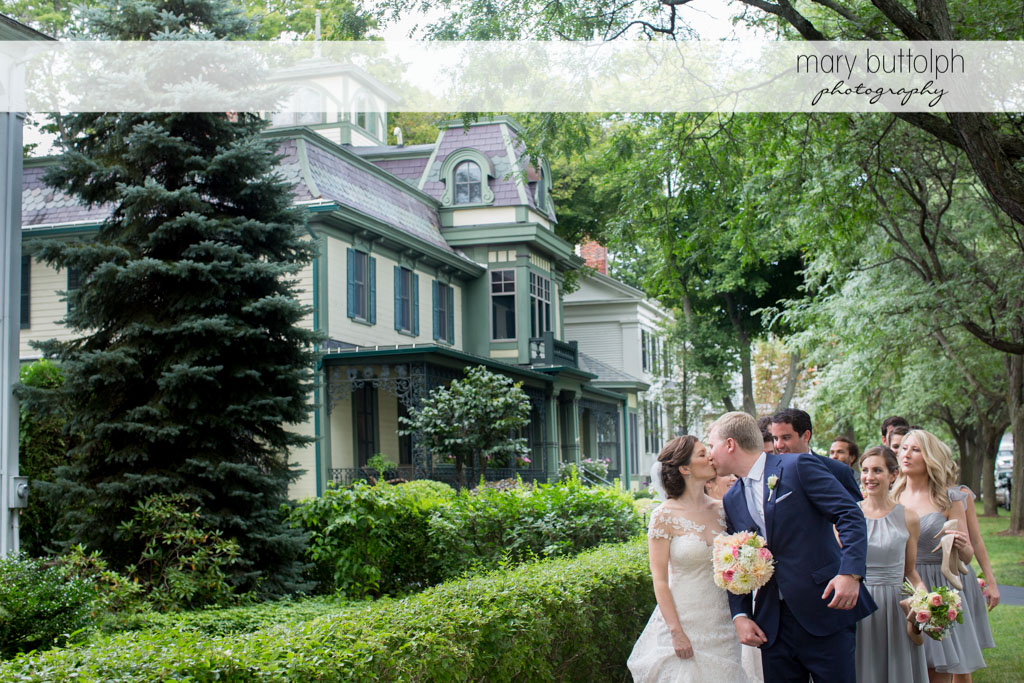 Couple kiss on the walkway with the wedding party behind them at Skaneateles Country Club Wedding