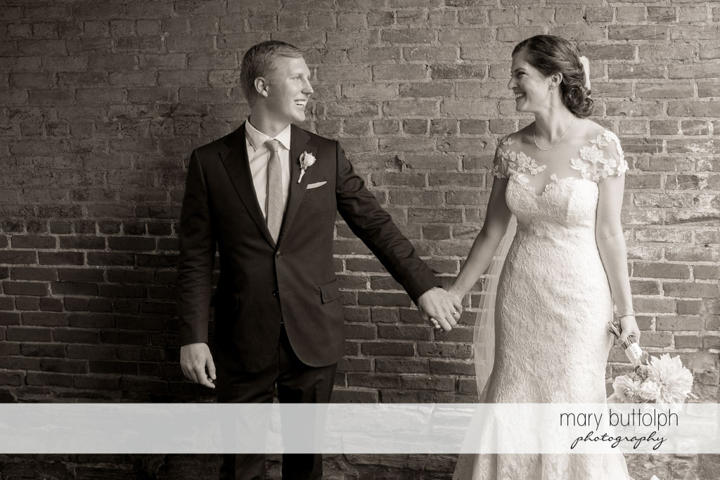 Couple hold hands in front of a brick wall at Skaneateles Country Club Wedding