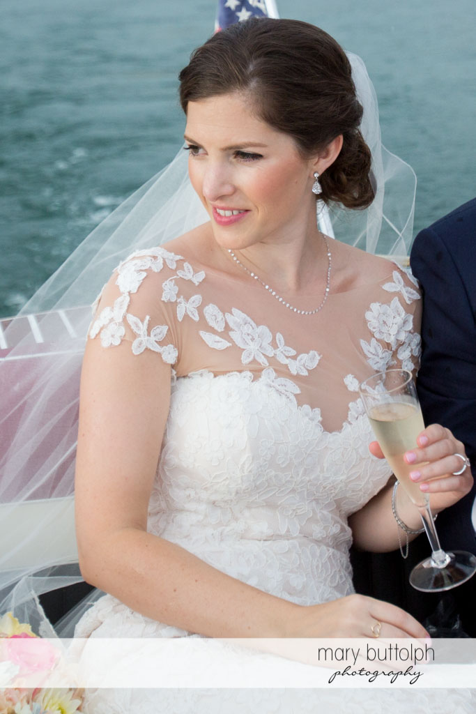 Bride enjoys the view while drinking wine by the lake at Skaneateles Country Club Wedding