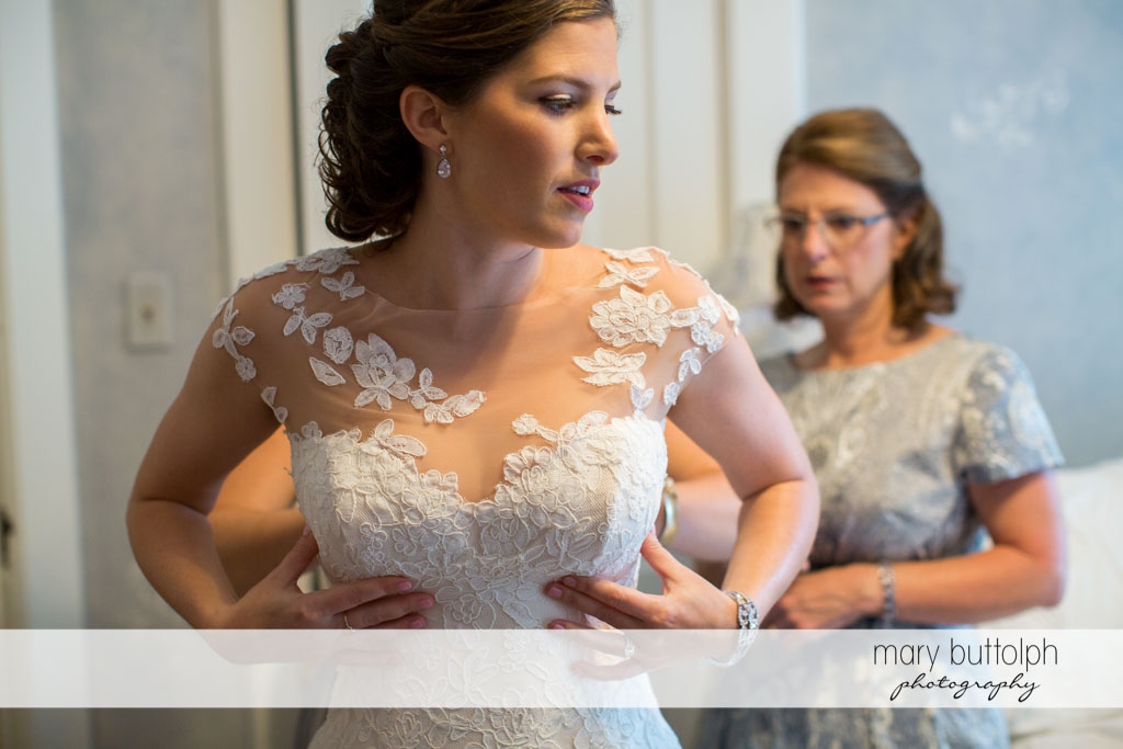 Bride gets a little help from her friends as she puts on her wedding dress at Skaneateles Country Club Wedding