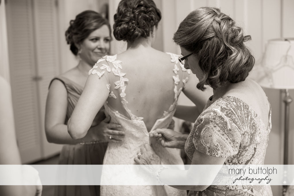 Bride slips on her wedding gown with the aid of relatives at Skaneateles Country Club Wedding