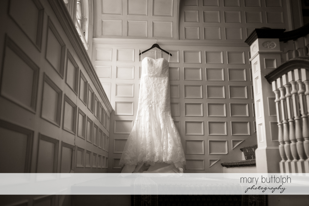 Bride's wedding dress hangs on the wall at the Brewster Inn Wedding