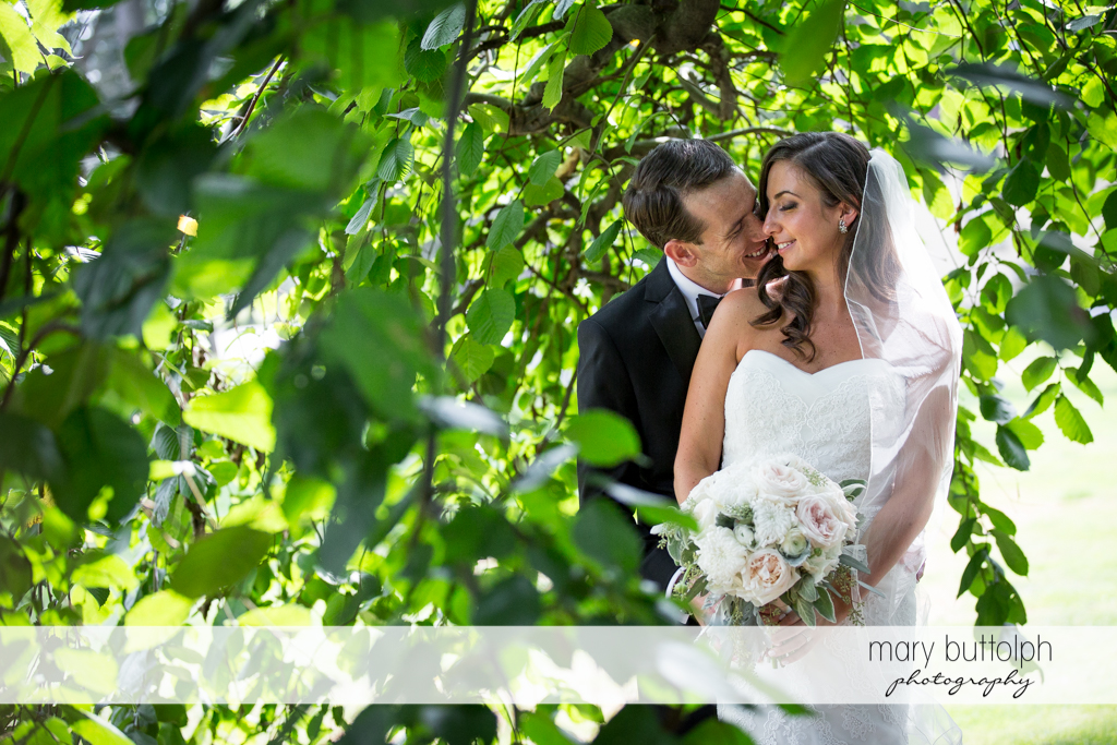 Couple pose under a tree in the garden at the Brewster Inn Wedding