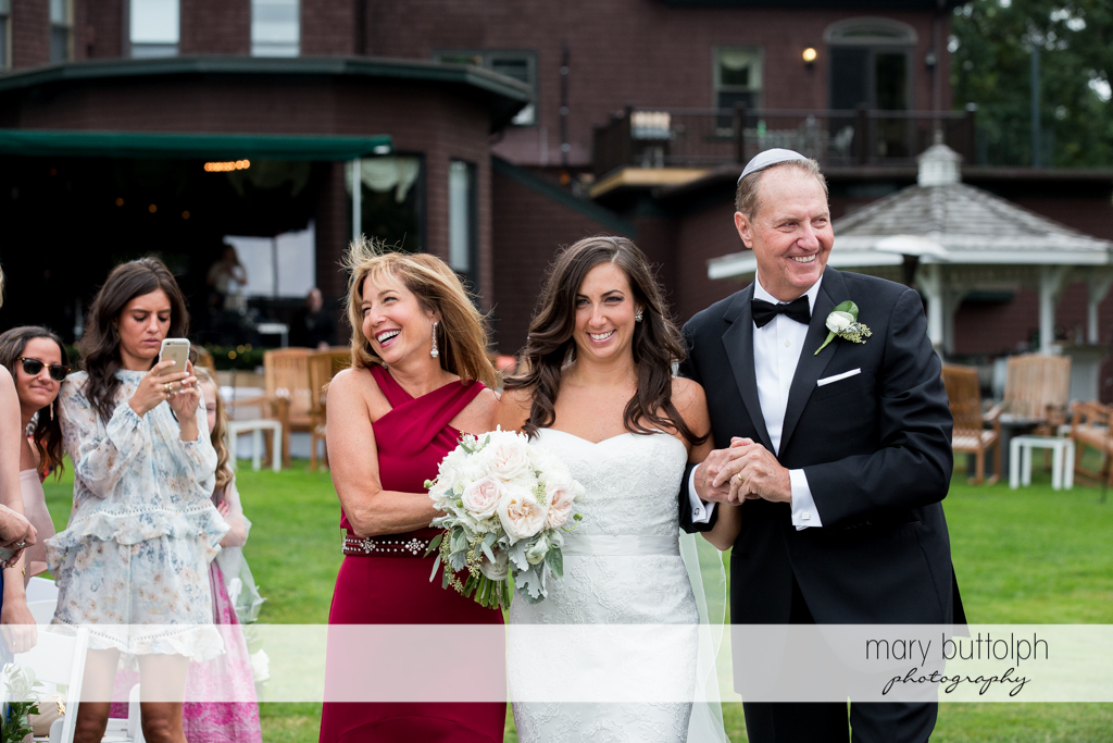 Bride is escorted by her parents to the wedding venue at the Brewster Inn Wedding