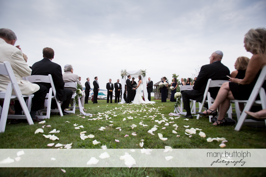 Flowers are strewn on the ground as the couple have a garden wedding at the Brewster Inn Wedding
